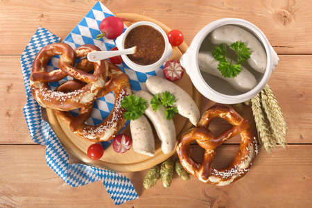 Bavarian veal sausage breakfast with sausages soft, pretzel and mild mustard on wooden board from Germany Standard-Bild