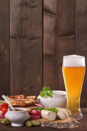 veal sausage: Bavarian veal sausage breakfast with sausages, wheat beer, soft pretzel on dark weathered wooden board from Germany Stock Photo