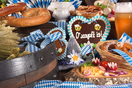 veal sausage: Many typical German Bavarian symbols in one picture. Gingerbread heart with The beer is tapped text, soft pretzels and Bavarian veal sausage.