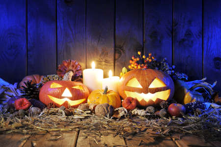 Illuminated Halloween pumpkins, candles, nuts, maize-cob and apple on straw in front of old weathered wooden board in blue light