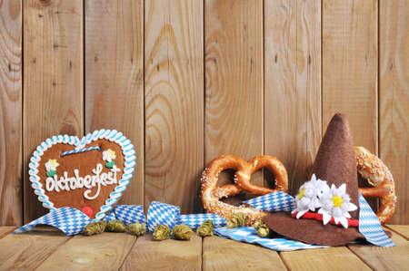 gingerbread heart: Oktoberfest - original bavarian gingerbread heart with Oktoberfesthat and soft pretzels from Germany in front of OLT wooden board