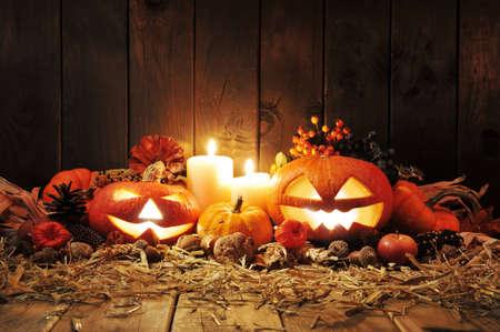 Kerze: Beleuchtete Halloween-K�rbisse, Kerzen, N�ssen, Maiskolben und Apfel auf Stroh vor der alten verwitterten Holztafel im Kerzenschein
