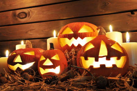 cucurbit: Four Illuminated Halloween pumpkins on straw in front of old weathered wooden board in candlelight