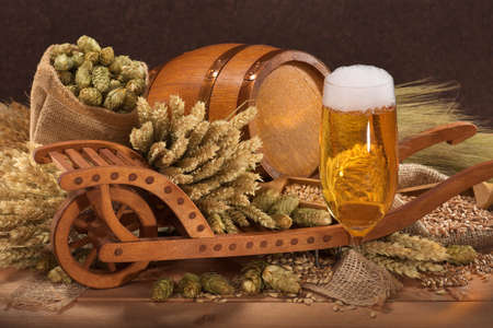 cebada: vaso de cerveza con un barril de madera con la carretilla, l�pulo, trigo, grano, cebada y malta Foto de archivo