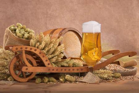 carretilla de mano: vaso de cerveza con un barril de madera con la carretilla, l�pulo, trigo, grano, cebada y malta Foto de archivo