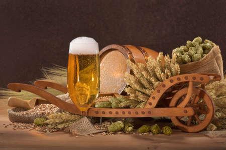 beer glass with wood barrel with wheelbarrow, hops, wheat, grain, barley and malt