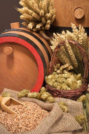 Three old wood beer barrels with hops, wheat, grain, barley and malt
