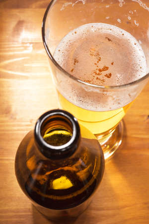 macro view of a beer glass with beer bottle on the table Stock Photo
