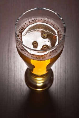 macro view of a beer glass with froth on the table
