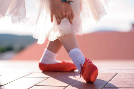 Feet of girl with red ballet shoes.