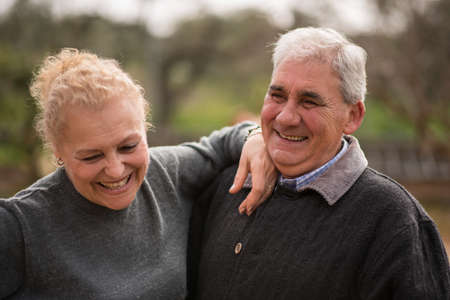 Beautiful and happy older couple, smiling outdoors on a Mediterranean winter day.
