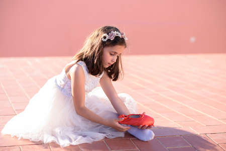 Girl sitting, with red ballet shoes, outdoors with sun on her back.