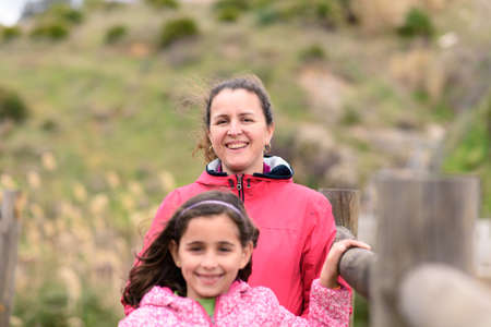 Mother and daughter, posing, happy in the countryside on a winter day, cloudy and cold.