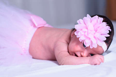 Baby girl with pink skirt and flower headband