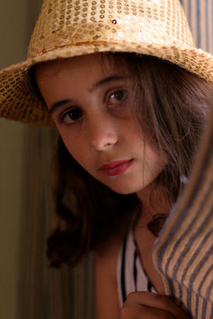 Close-up in interior of girl with brown hair posing with a golden hat