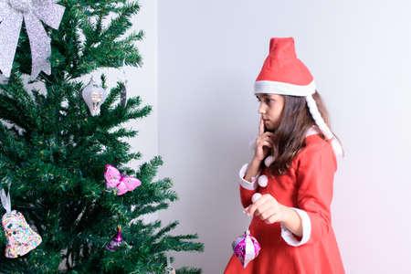 Bambina che decora l'albero di Natale su sfondo bianco