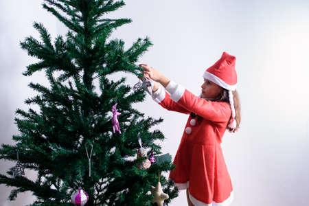 Kleines Mädchen, das Weihnachtsbaum schmückt. Als Weihnachtsmann verkleidet. Auf weißem Hintergrund