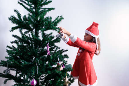Little girl decorating Christmas tree. Disguised as Santa Claus. On white background
