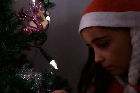 Close-up of pretty girl dressed as Santa Claus illuminated with Christmas tree lights.