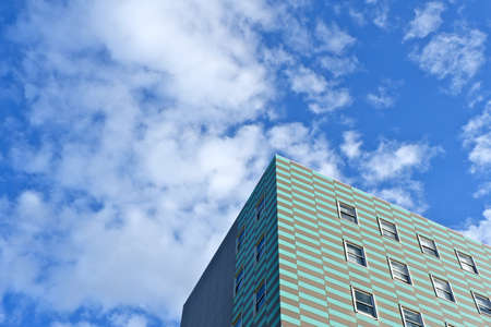 Simple urban background. Corner of the tiled green and grey building against the blue sky