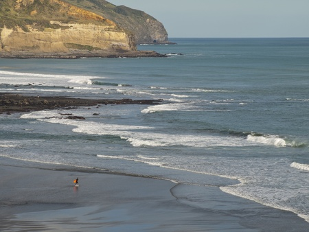 Surfer at Maori Bay, Coastal view, West Coast, North Island New Zealand photo