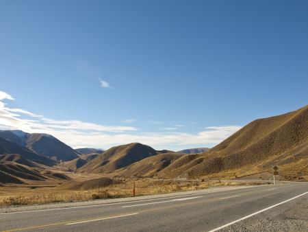 mountain road on clear sunny day of autumn, South Island, New Zealand
