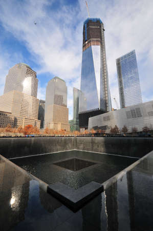 Daytime photo of the World Trade Center Memorial towards the new 1 World Trade Center under construction.