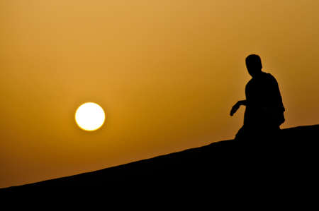 Kneeling man, overlooking sunset in the deserts of Dubai, UAE