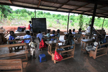 Students attending class in an outdoors elementary school classroom in the Yilo Krobo District not far from Accra, Ghana on November 14, 2011  Dirt floor  Mud baked bricks building  Sajtókép