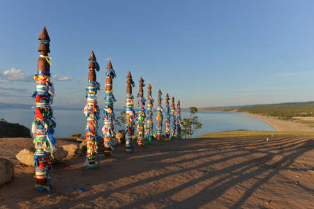 Buryat traditional pagan holy poles by Lake Baikal  A row of vertical logs with colored rags at sunset with their shadows stretching out