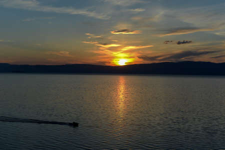 A Boat passing the Sunset on Lake Baikal from Olkhon Island on a summer day  photo