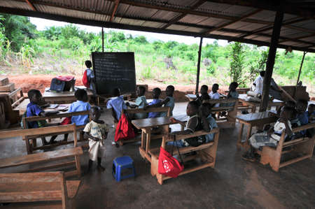 ASIAFO AMANFRO, EASTERN, GHANA - NOVEMBER 14  Students attending class in an outdoors elementary school classroom in the Yilo Krobo District near Accra, Ghana on November 14, 2011  Mud brick building