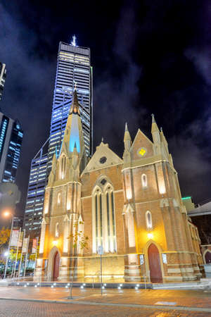 wesley: Wesley Church, Perth, Australia at night, with the skyline in the background. It is one of the oldest church buildings and one of few remaining 19th-century colonial buildings in the City of Perth. Stock Photo