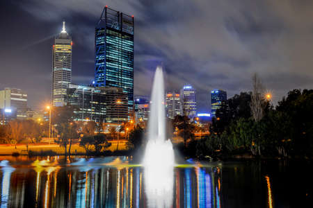 perth: Skyline of Perth, Australia. View from John Oldany park. Australian skyscrapers and lights reflected in the water. Stock Photo