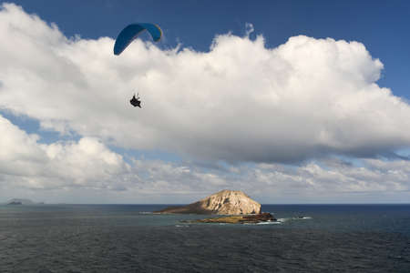 Manana and Kaohikaipu Islands, commonly known as Rabbit and Turtle Islands, off the coast of Oahu, Hawaii. Hanglider floating in the wind. photo