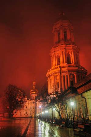 enveloped: View of Kiev Pechersk Lavra and the Bell Tower in Ukraine at night, enveloped in fog