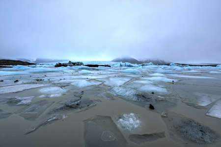 fjallsarlon: View of Fjallsarlon Glacial lake full of floating icebergs near the Fjallsjokull glacier on a cloudy day, Iceland