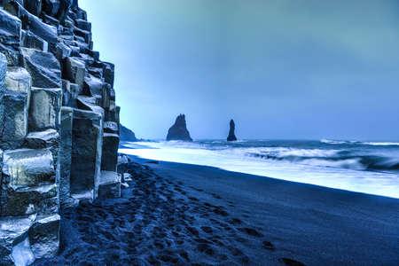 Wide view of Reynisdrangar rock formations on Reynisfjara Beach at dusk, Halsanefhellir, Iceland  photo