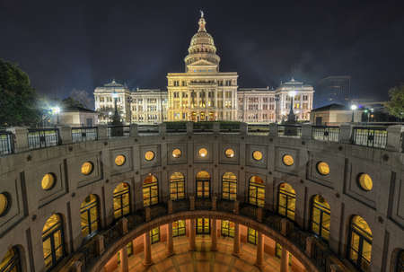 and distinctive: The Texas State Capitol Building with a view of the modern extension in downtown Austin at Night. The building was built in 1882-1888 of distinctive sunset red granite.