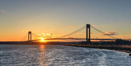 boroughs: Verrazano Narrows Bridge At Sunset from Brooklyn. The bridge a double-decked suspension bridge that connects the boroughs of Staten Island and Brooklyn in New York City at the Narrows.