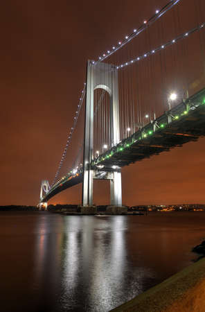 boroughs: Verrazano Narrows Bridge at night from Brooklyn. The bridge a double-decked suspension bridge that connects the boroughs of Staten Island and Brooklyn in New York City at the Narrows.