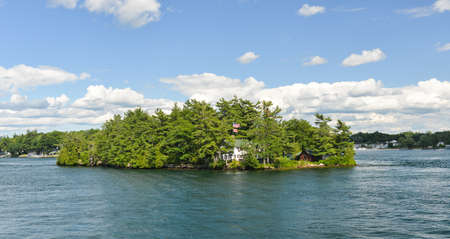 House in the Thousand Islands on Saint Lawrence River with USA and Canadian flags. photo