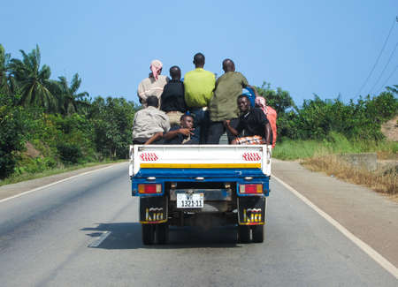 typical: TAKORADI, GHANA - NOVEMBER 12, 2011: Typical Ghanaian Pickup Truck with workers on the road.