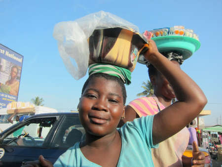 ACCRA, GHANA - NOVEMBER 13, 2011: Typical Street Vendor on the roads of Accra selling goods to passing drivers. 新聞圖片