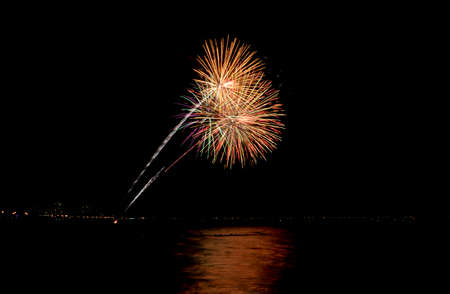 Coney Island Fireworks on the beach on a summer evening reflecting in the Atlantic Ocean. Imagens