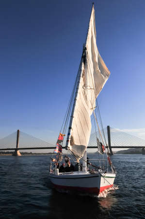 ASWAN, EGYPT - DECEMBER 29: A Felucca sail under Aswan bridge in Aswan, Egypt on December 29, 2008. Aswan bridge completed in 2002 and its total length is 977 m.