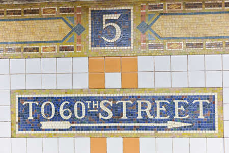 NEW YORK, NEW YORK - OCTOBER 27, 2014: Classic mosaic tile of the Fifth Avenue Subway Station, New York. Sign showing exit to 60th Street.