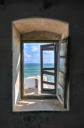 Window view from Cape Coast Castle, a fortification in Ghana built by Swedish traders for trade in timber and gold. Later the structure was used in the trans-Atlantic slave trade. Editorial