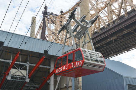queensboro bridge: NEW YORK, NY - JANUARY 19, 2013: The famous Roosevelt Island cable tram car that connects Roosevelt Island to Manhattan alongside the Queensboro Bridge along Manhattan, New York City.