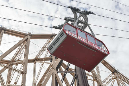 roosevelt: NEW YORK, NY - JANUARY 19, 2013: The famous Roosevelt Island cable tram car that connects Roosevelt Island to Manhattan alongside the Queensboro Bridge along Manhattan, New York City.